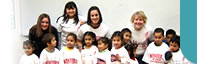 Western Oregon University (WOU) Students with Latino children enrolled in a preschool program called Lecturas en Familia (Family Readings). This is a program developed by the Farmworker Housing Development Corporation at Colonia Amistad in Independence, OR.  On this day, WOU students taught a lesson plan that included painting WOU shirts donated by the WOU bookstore.