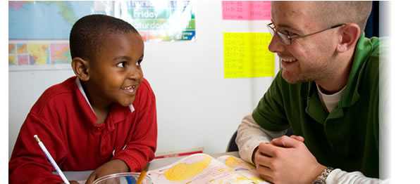 A Virginia Tech student participating in Homework Help with a Somali Bantu child at the Pilot Street Project in Roanoke, VA; a project sponsored by the Center for Student Engagement and Community Partnerships.